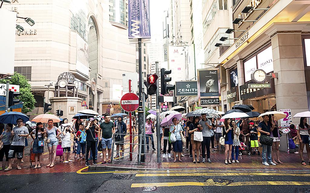 Människor väntar på att gå över gata i Hong Kong