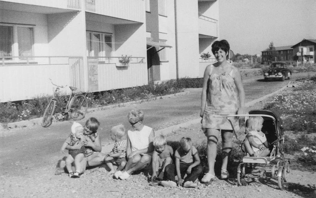 Kvinna med barn utanför hyreshus
