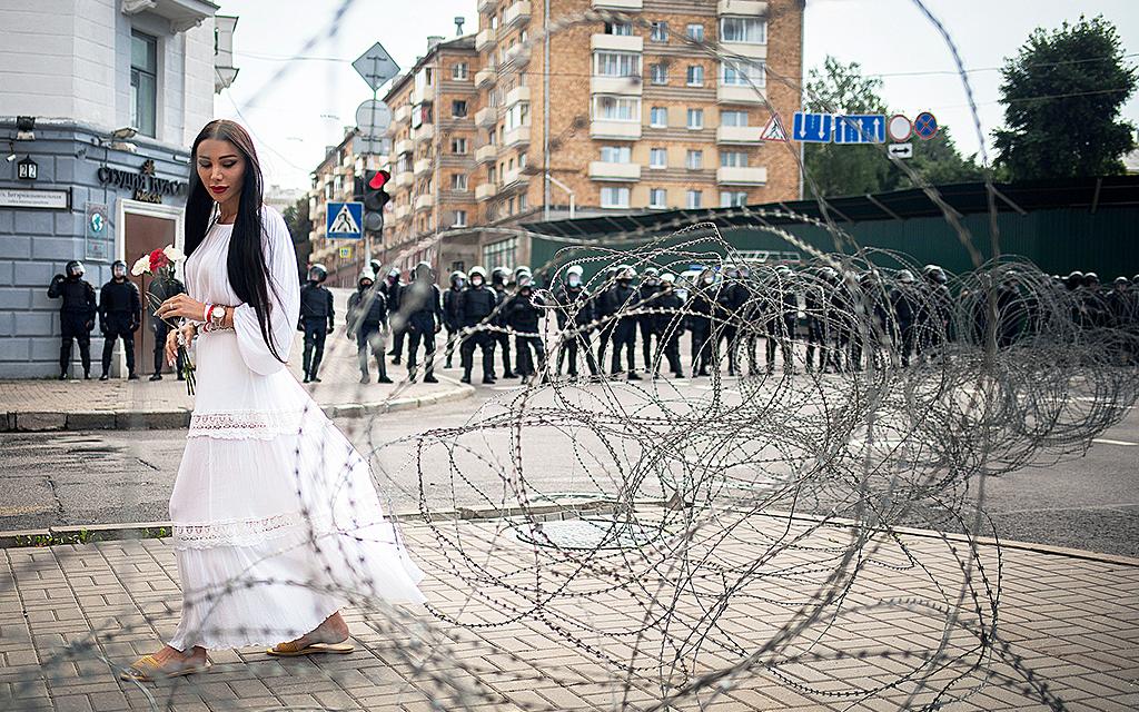 Kvinna i vit klänning framför taggtråd i Belarus. I bakgrunden militärer.