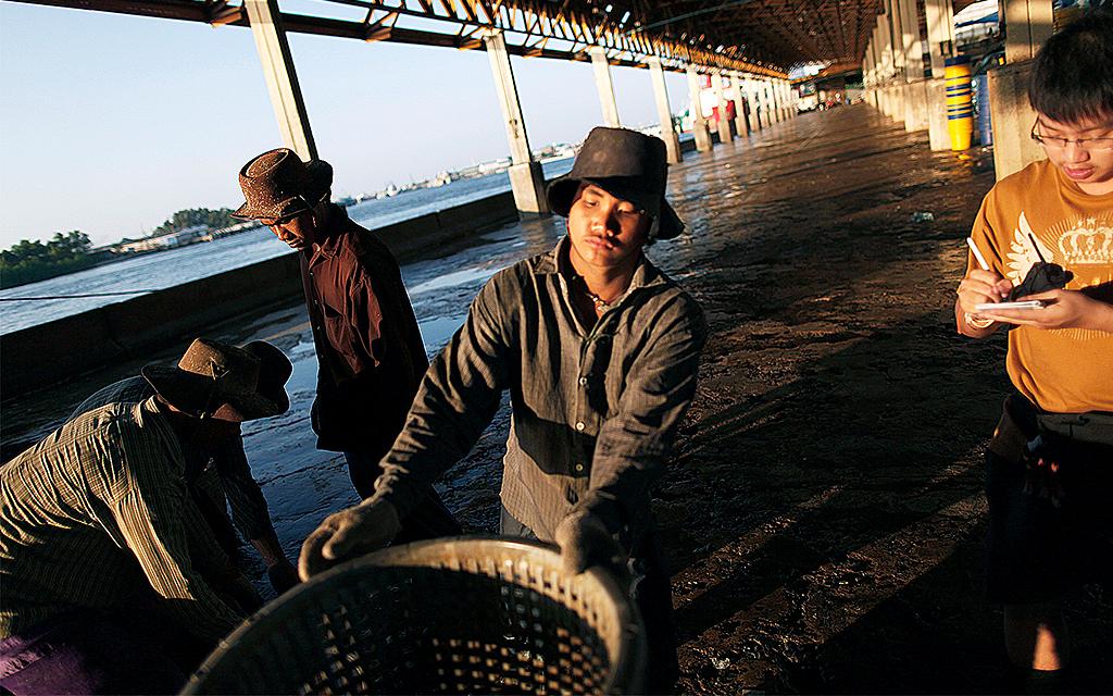 Migranter från Myanmar lossar fisk på brygga i Thailand