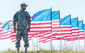 Soldat framför rad av amerikanska flaggor