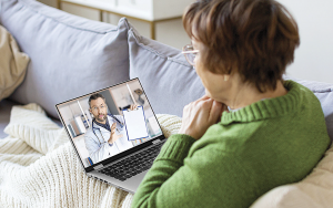 Kvinna konverserar med läkare via bärbar dator
