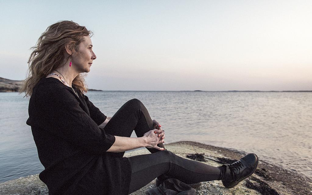 Linda Lindmark sitter på en klippa och tittar ut mot havet