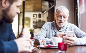 Äldre man med smartphone på kafé